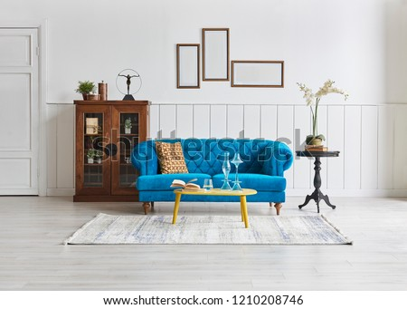 Modern living room blue armchair and white classic pattern wall. Wooden cabinet black coffee table and home decoration. #1210208746