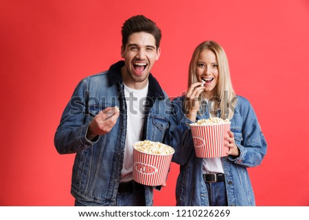 Portrait of a happy young couple dressed in denim jackets standing together isolated over red background, watching movie, eating popcorn #1210226269