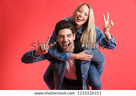 Portrait of a happy young couple dressed in denim jackets standing together isolated over red background, piggyback ride, showing peace #1210226311