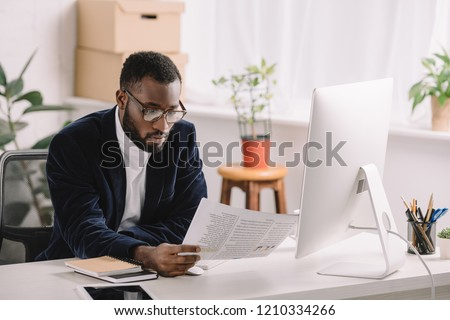 stylish african american businessman holding document and working with computer in office  #1210334266