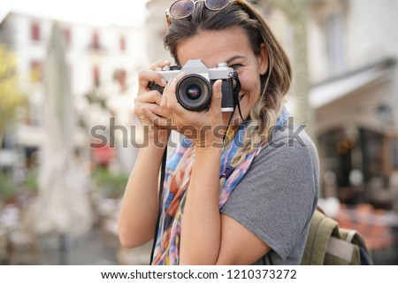 Young woman taking photographs on SLR                               Royalty-Free Stock Photo #1210373272