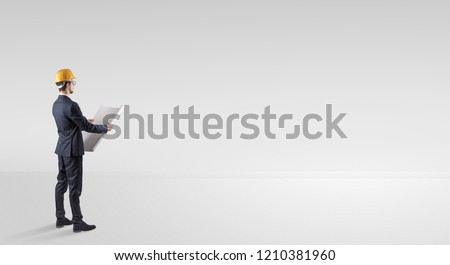 Young architect with construction helmet standing in an empty space and holding a plan #1210381960