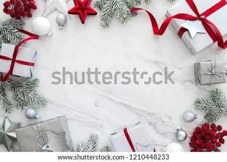 Merry Christmas and Happy Holidays greeting card, frame, banner. New Year. Christmas silver handmade gift boxes on white marble background top view. Winter holiday theme. Flat lay. #1210448233