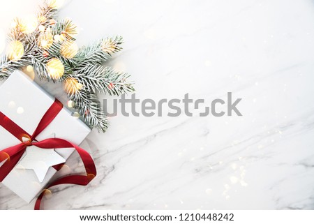 Merry Christmas and Happy Holidays greeting card, frame, banner. New Year. Christmas silver handmade gift boxes on white marble background top view. Winter holiday theme. Flat lay. #1210448242