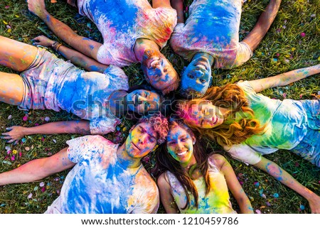 Group of happy friends playing with holi colors in a park - Young adults having fun at a holi festival, concepts about fun, fun and young generation #1210459786