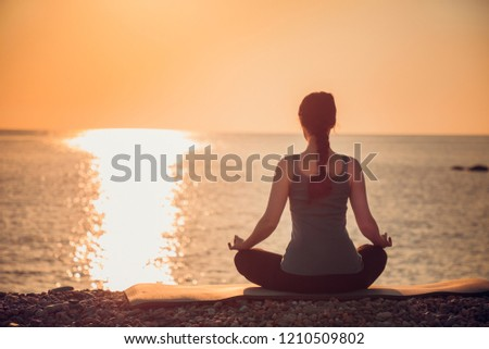 Woman practicing yoga lotos position. Sunset over sea in the background. #1210509802