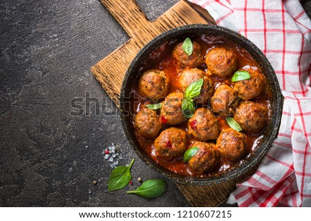 Meatballs in tomato sauce in a frying pan on dark stone table. Top view copy space. #1210607215