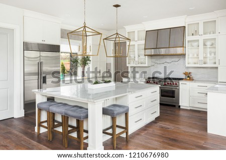 Beautiful white kitchen in new luxury home. Features large island,pendant lights, and hardwood floors #1210676980