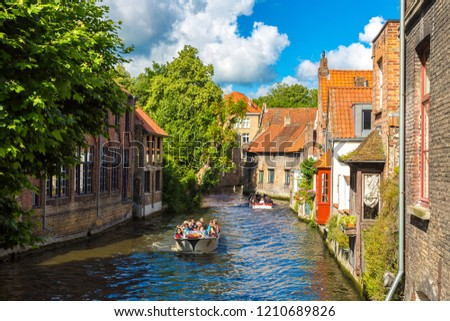 BRUGES, BELGIUM - JUNE 14, 2016: Tourist boat on canal in Bruges in a beautiful summer day, Belgium on June 14, 2016 #1210689826