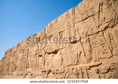 The wall of the ancient Egyptian temple of Karnak (founded 3500 years BC) with hieroglyphs carved on it and figures of pharaohs and gods. #1210697968