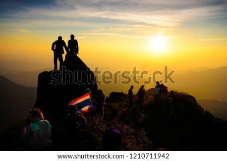 Nakhon Sawan,Thailand - January 7, 2013:Many people Watching the sunset.Some still stand on the sailboat stone. at Mokochu Peak in Mae Wong National Park,Nakhon Sawan,Thailand. #1210711942