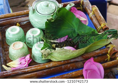 Vintage antique celadon glazed porcelain tea set with lotus flower tea on a lotus leaf and pink lotus petals on a bamboo tray #1210742173
