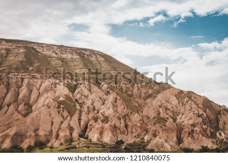 Epic landscape view over Cappadocia, located among the fairy chimney and volcanic rock formations clustered with spectacularly coloured valleys nearby. #1210840075