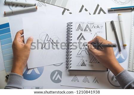 Graphic designer drawing sketch design creative Ideas draft Logo product trademark label brand artwork. Graphic designer studio Concept. #1210841938