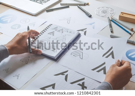 Graphic designer drawing sketch design creative Ideas draft Logo product trademark label brand artwork. Graphic designer studio Concept. #1210842301