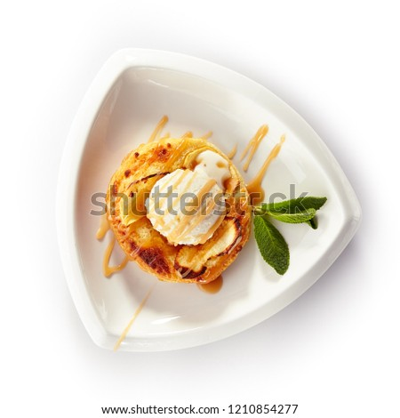 Round Apple Pie or Tart Topped with Ice Cream Ball and Sweet Sauce in White Plate Isolated. Frozen Yogurt on Fresh Crisp Puff or Mini Cake Decorated with Mint Leaves on a Light Background #1210854277