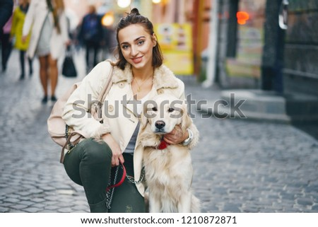 beautiful woman walking her dog in the city during the day #1210872871