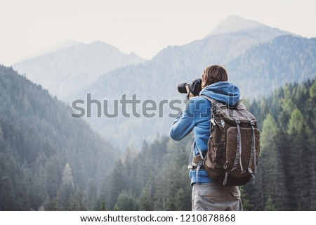 Young cheerful man photographer taking photographs with digital camera in a mountains. Travel and active lifestyle concept Royalty-Free Stock Photo #1210878868