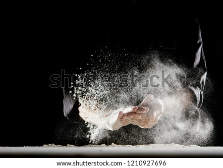 Powdery flour flying into air as man in black chef outfit wipes off his hands over white table covered in flour #1210927696