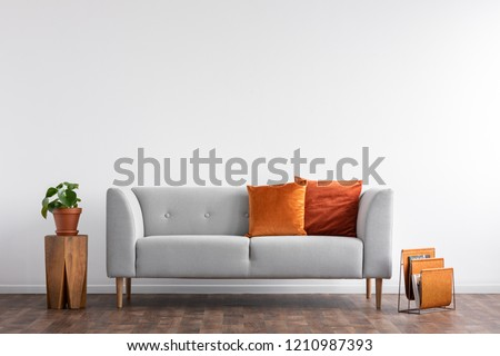 Comfortable couch with orange and red pillow in spacious living room interior, real photo with copy space on the empty white wall Royalty-Free Stock Photo #1210987393