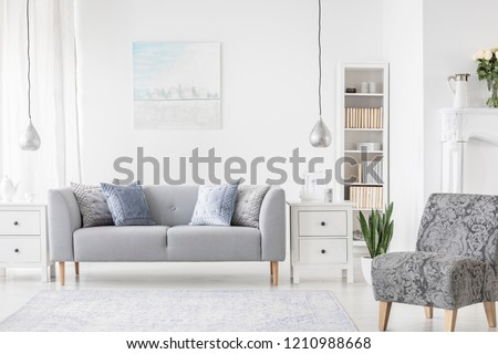 Lamp above white cabinet between plant and grey sofa in simple flat interior with armchair. Real photo #1210988668