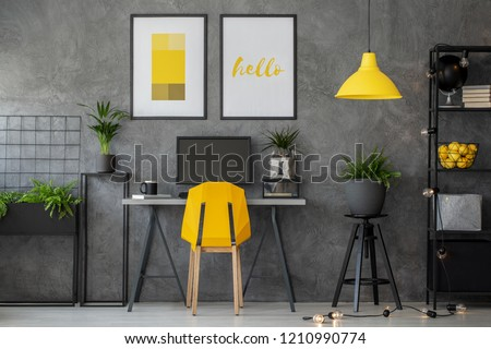 Stylish yellow and grey home office with industrial furniture and urban jungle, real photo with posters on concrete wall #1210990774