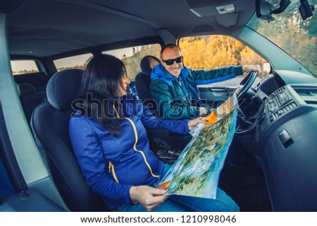 young couple traveling by car through the picturesque autumn forest. transport concept #1210998046