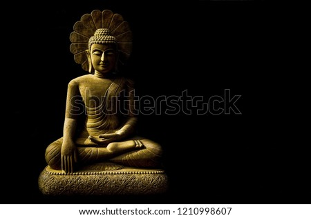 Statue of Buddha sitting in meditation with black space on the left hand side