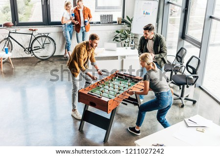 high angle view of young casual business people playing table football at office and having fun together Royalty-Free Stock Photo #1211027242