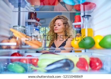 Woman taking food from fridge full of groceries. Picture taken from the inside of fridge.