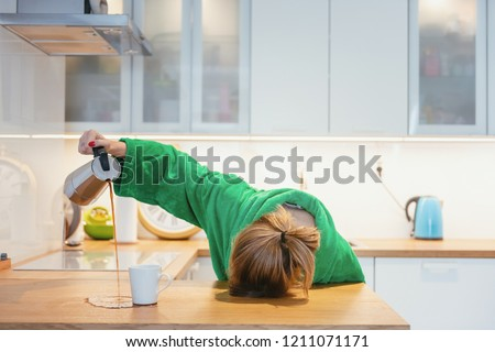 Tired woman sleeping on the table in the kitchen at breakfast. Trying to drink morning coffee #1211071171