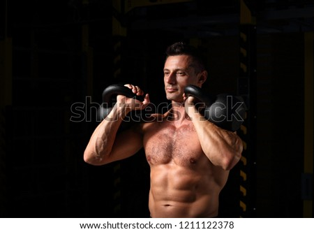 Handsome strong man doing the exercises with kettlebells on dark shadow background. Closeup contrast portrait. #1211122378