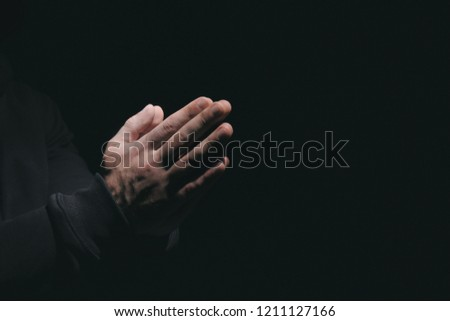 Hands of religious man praying on black background #1211127166