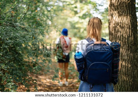 Backshot of Young woman on hiking with backpack in forest #1211131072