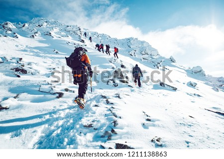 A group of climbers ascending a mountain in winter Royalty-Free Stock Photo #1211138863