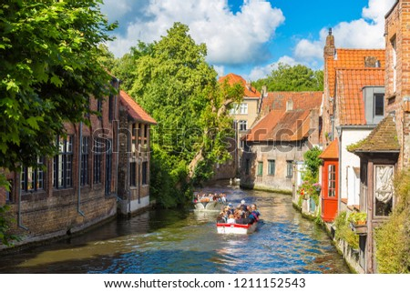 BRUGES, BELGIUM - JUNE 14, 2016: Tourist boat on canal in Bruges in a beautiful summer day, Belgium on June 14, 2016 #1211152543