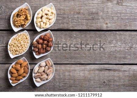 Mix of nuts : Pistachios, almonds , walnuts , pine nut , hazelnuts and cashew . Snack in bowl backgrond #1211179912