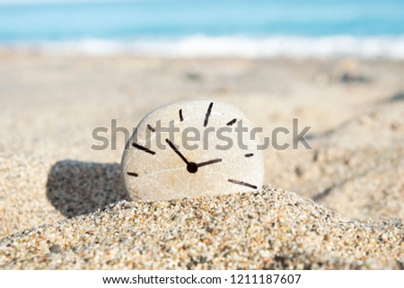 closeup of a round stone with a clock, drawn by myself, in it on the sand of a beach, with the sea in the background #1211187607