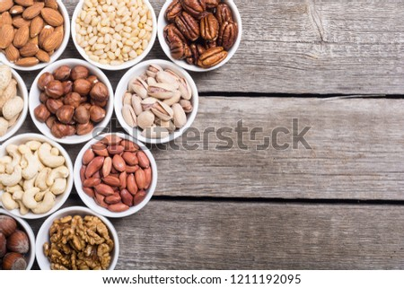 Mix of nuts : Pistachios, almonds , walnuts , pine nut , hazelnuts and cashew . Snack in bowl backgrond #1211192095