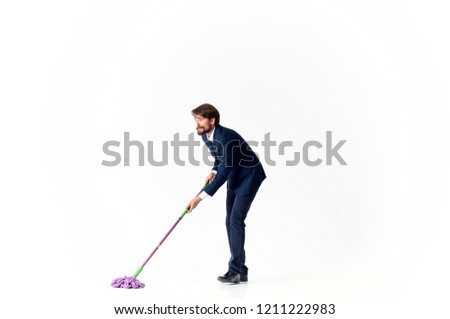 man in suit washes floor with a mop                         #1211222983