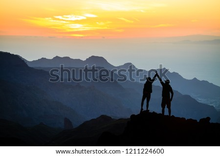Teamwork couple helping hand trust help, silhouette success in mountains. Team of climbers man and woman. Hikers celebrate with hands up, help each other on top of mountain, sunset landscape. #1211224600