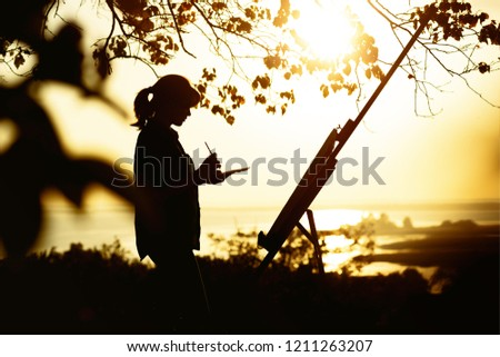 silhouette of a young woman painting a picture with paints on canvas on an easel outdoors, girl profile with paint brush and palette engaged in art on the nature in a field at sunset #1211263207