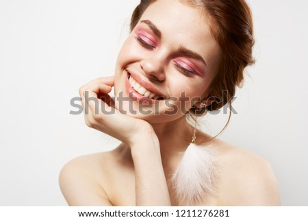 cheerful woman with bright makeup and fluffy earrings                             #1211276281