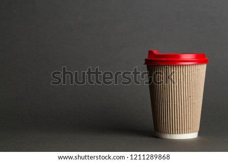 coffee to go in a disposable cup on a black background, place for text #1211289868