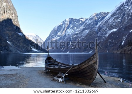 Photo taken in Norwegian Fjords of a viking boat in front of water and mountains.