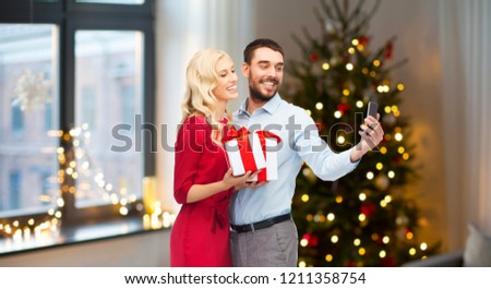 technology and holidays concept - happy couple with gifts taking selfie by smartphone over home room and christmas tree background #1211358754