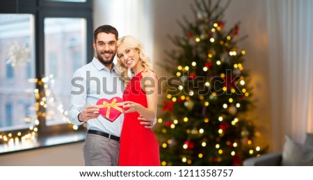people and holidays concept - happy couple with heart shaped gift box over home room and christmas tree background #1211358757