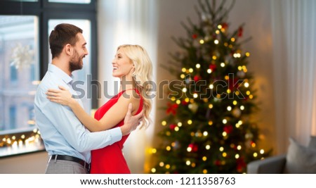 love and holidays concept - happy couple hugging over home room with christmas tree background #1211358763