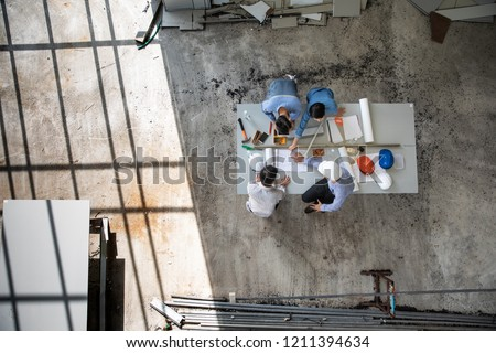 Four persons professional team of engineers talk together to review material in construction site, taken from above high angle, top view photo with shadow of window frame on floor.