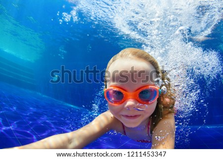 Happy family in swimming pool. Smiling child in goggles swim, dive in pool with fun - jump deep down underwater. Healthy lifestyle, people water sport activity, swimming lessons on holidays with kids #1211453347